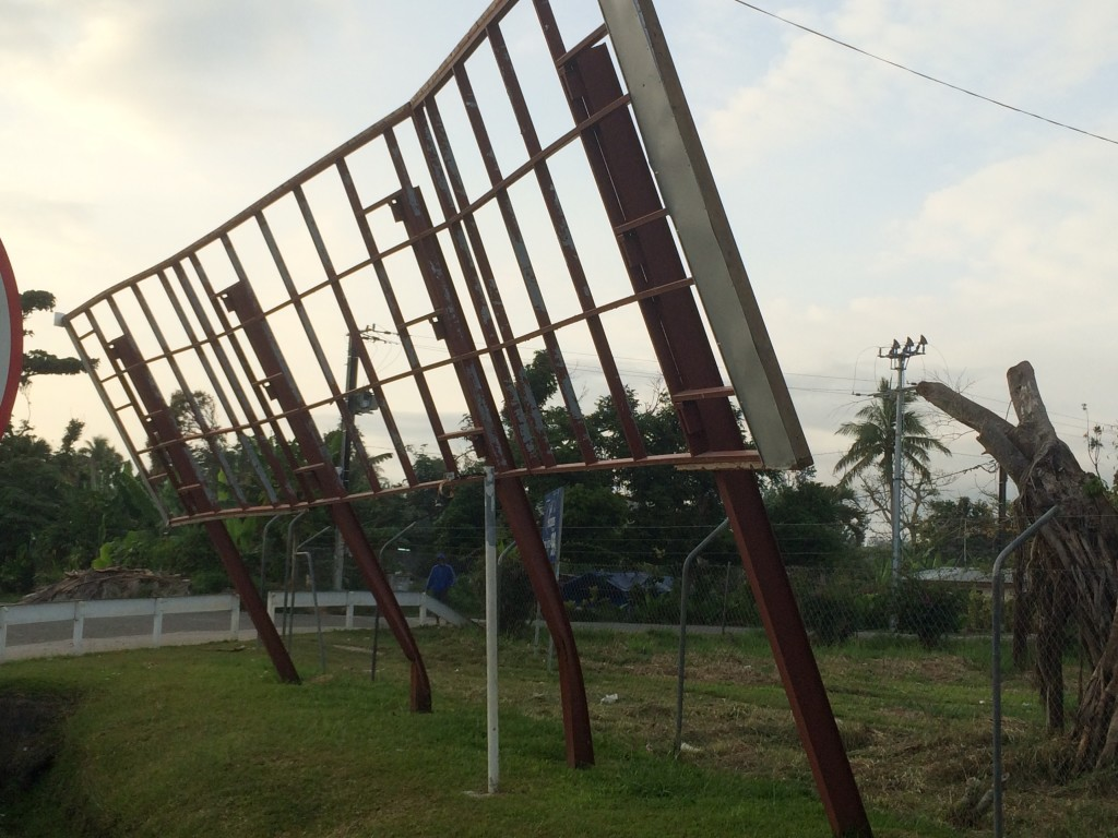 A sign buckles under the winds that passed with Cyclone Pam only 7 months ago.