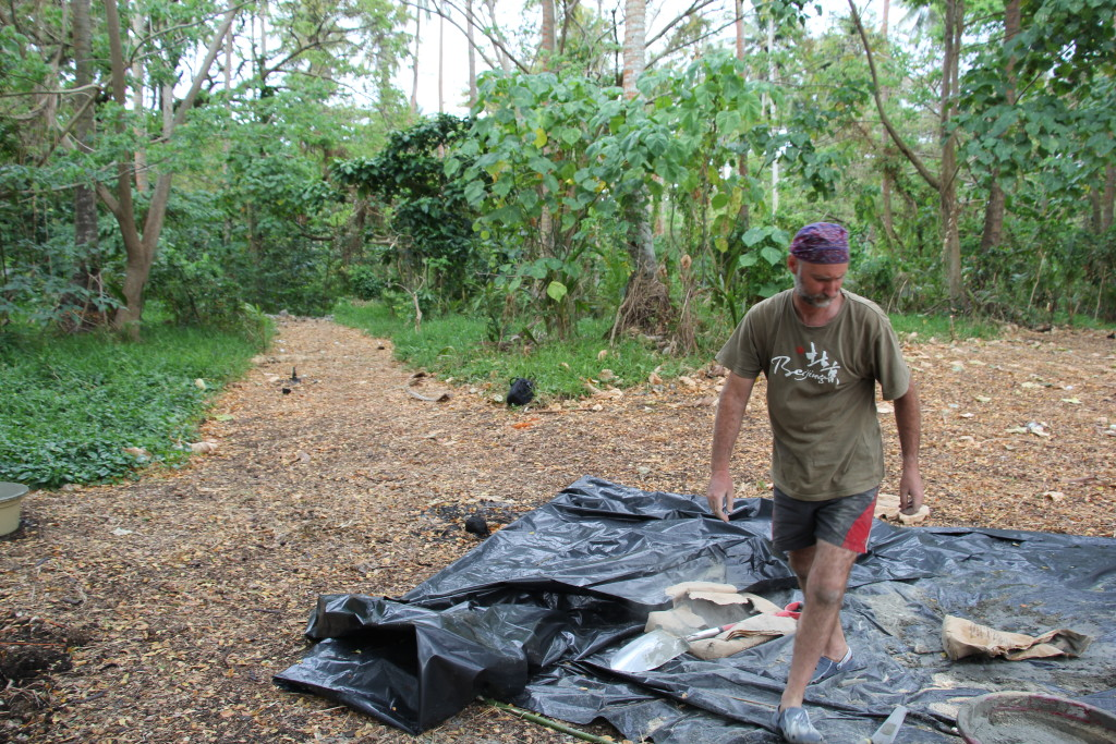 The race to beat the rain is on as Wayne prepares the Polythene to mix concrete.